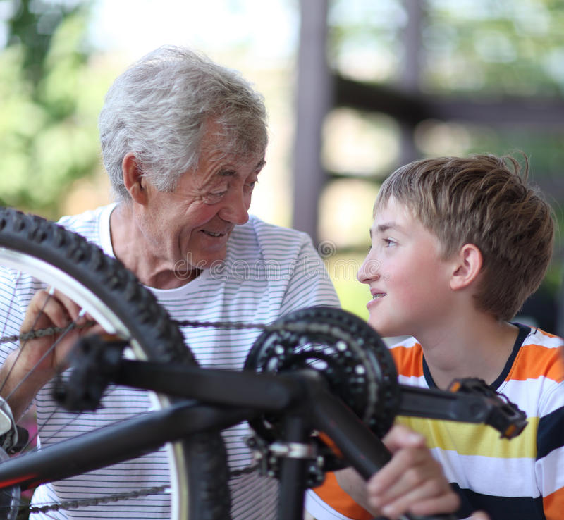 Boy and grandfather fixing bike royalty free stock image