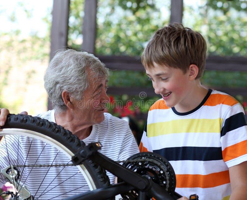 Boy and grandfather fixing bike stock photo