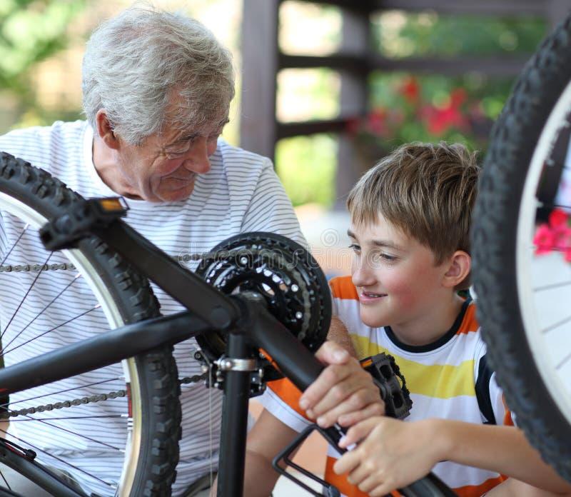 Boy and grandfather fixing bike stock image