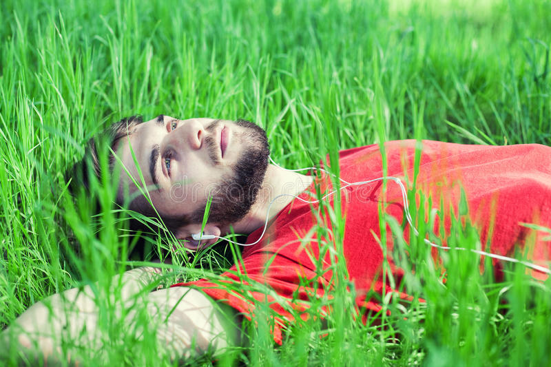 Boy in a grass. The boy in a green grass listens to music royalty free stock photography