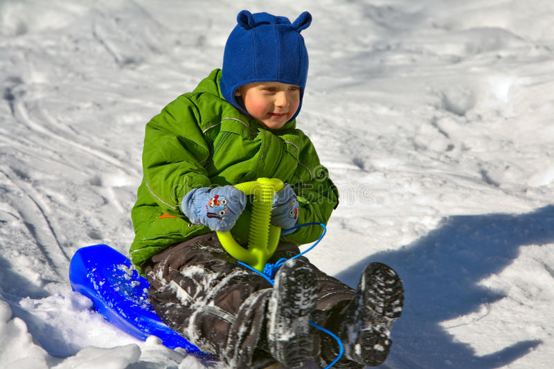 Boy in green on the sledge (3) stock images