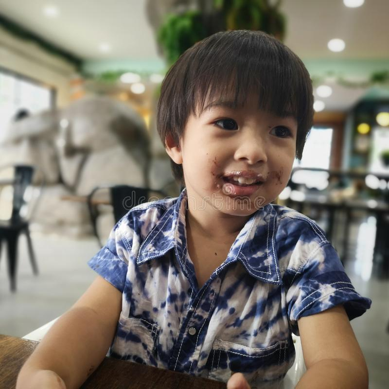 The boy had ate a chocolate. The boy had ate a chocolate stain on his mouth stock photo