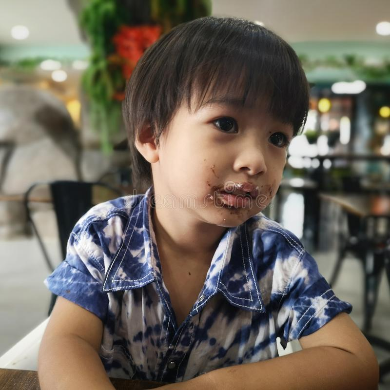 The boy had ate a chocolate. The boy had ate a chocolate stain on his mouth stock photography
