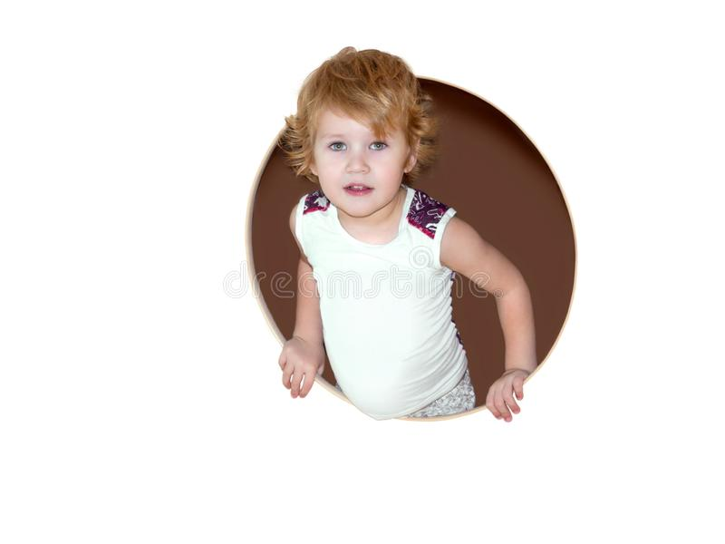 Boy half climbed out into the round window and smiles contentedly right into the frame royalty free stock images