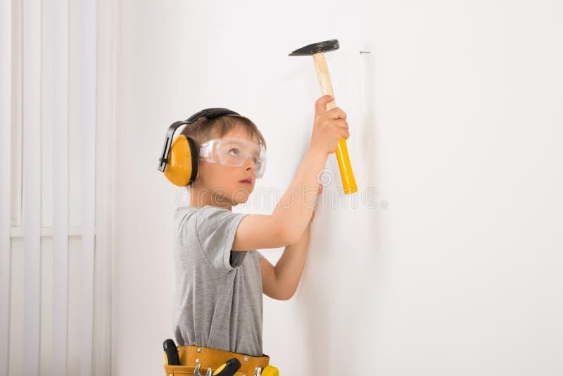 Boy Hammering Nail In Wall stock photo