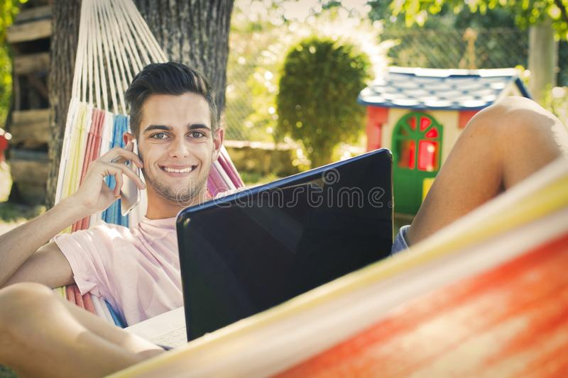 Boy in hammock with laptop royalty free stock photos