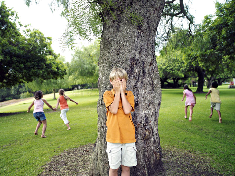 Boy (7-9) with hands covering eyes playing hide and seek in park, hiding from friends behind tree royalty free stock photo