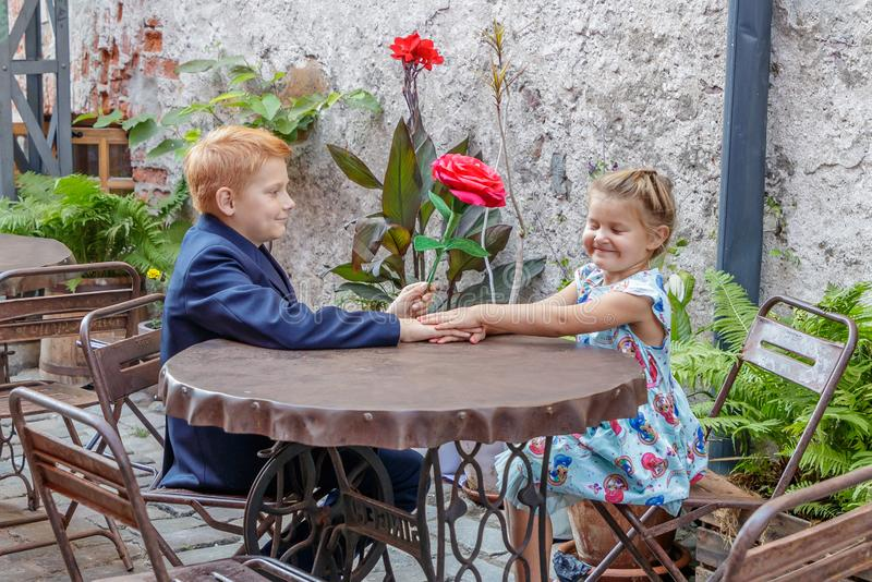 Boy gives girl a red flower stock photos