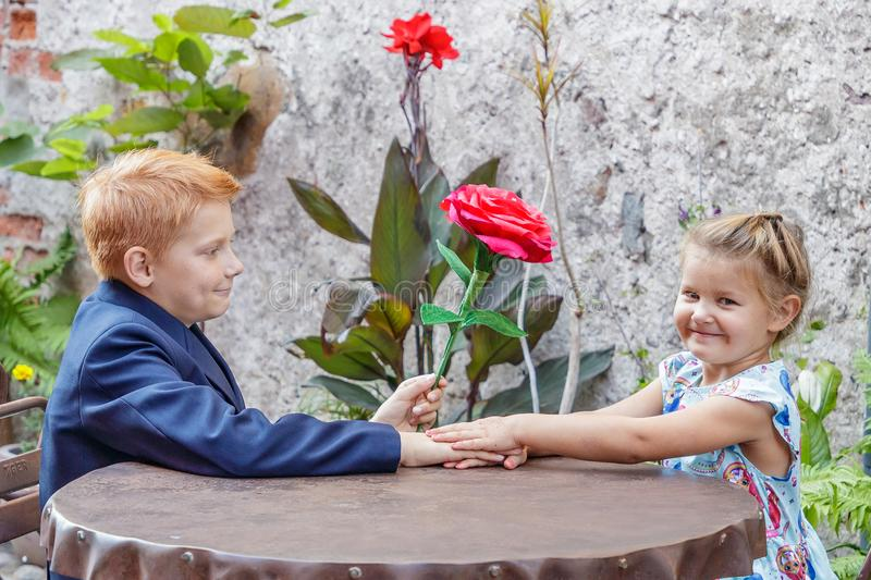 Boy gives girl a red flower royalty free stock photo