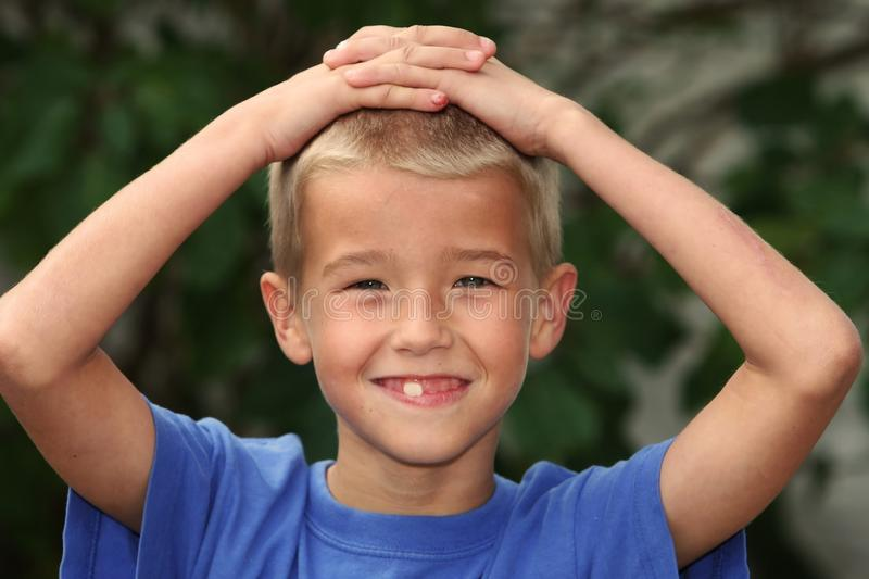 Boy with Hands on Head. Young lad in blue t-shirt with hands on his head royalty free stock photos