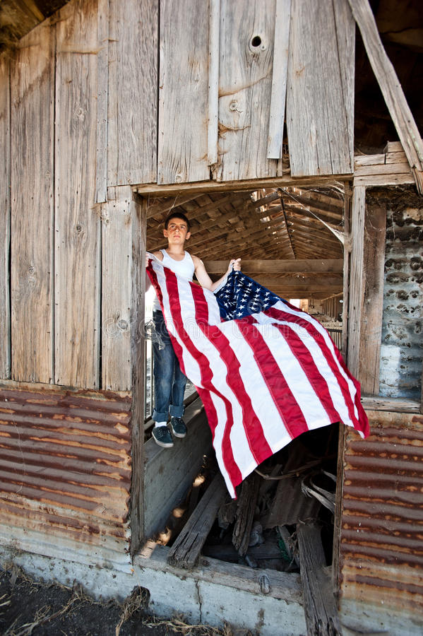 Boy hanging American flag. A patriotic teenager gets ready to hang an American flag on an old rustic barn stock photo