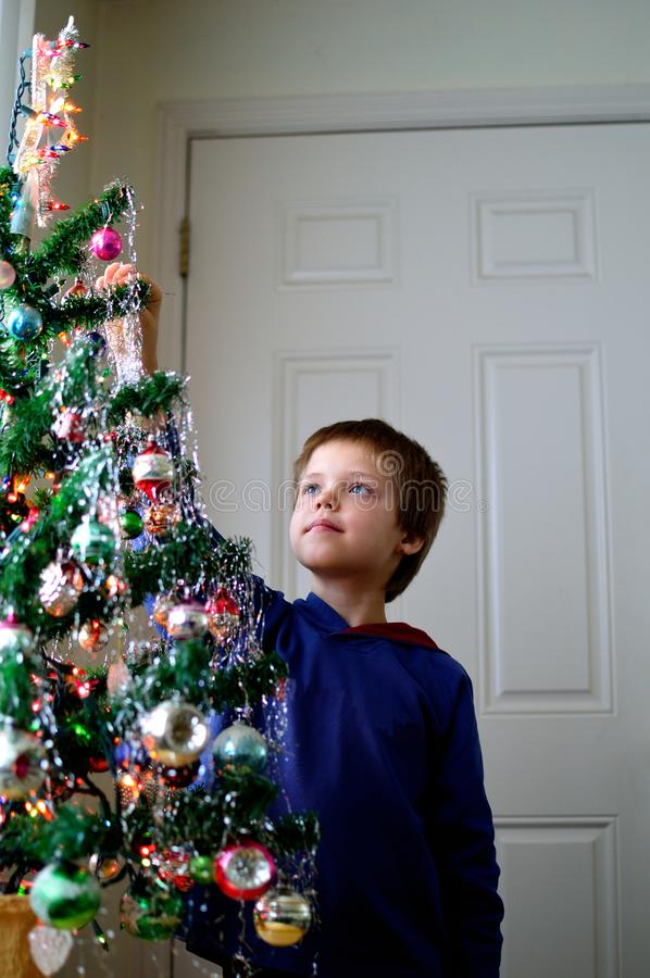 Boy hanging icicles on Christmas Tree decorating. Eight year old boy helps decorate the family Christmas tree putting on sliver icicles ornaments as he gazes at stock photo