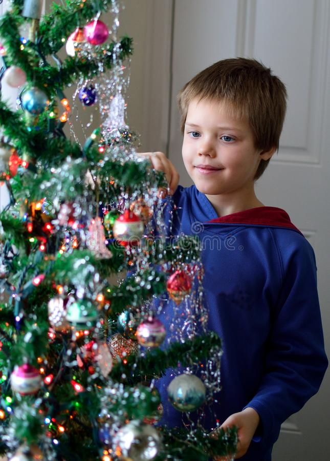 Boy hanging icicles on Christmas Tree holiday decorating royalty free stock photos
