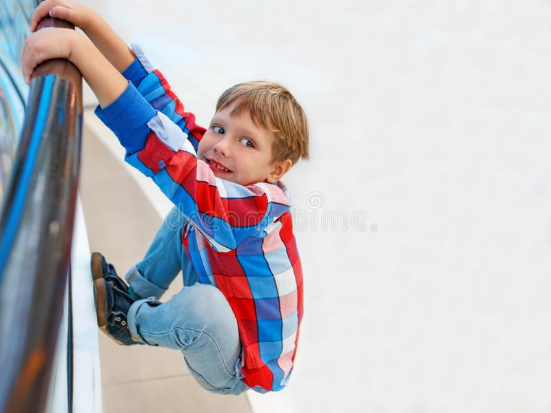 Boy is hanging on the railing of the bridge, child playing in a park stock photography