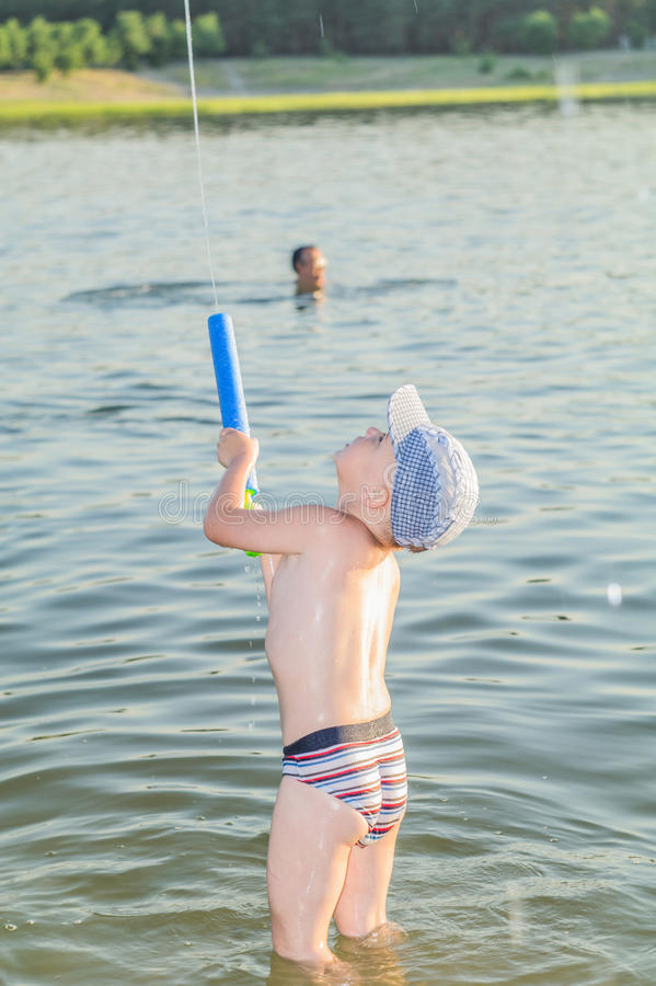The boy is happy. SEVERODONETSK - 13 JUNE 2015, Lugansk region Ukraine, boy Cyril, at the age of 4 years, bathes in lake and sends to the sky a water stream stock photo