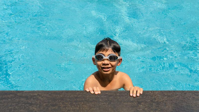 Boy happy swimming in a pool. Beautiful little boy swimming at the pool. royalty free stock image