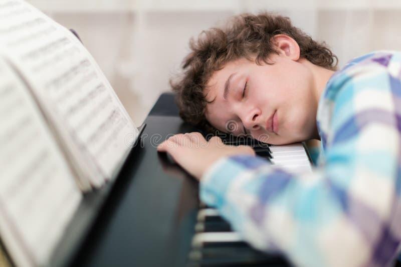 The boy has fallen asleep on the piano stock photos