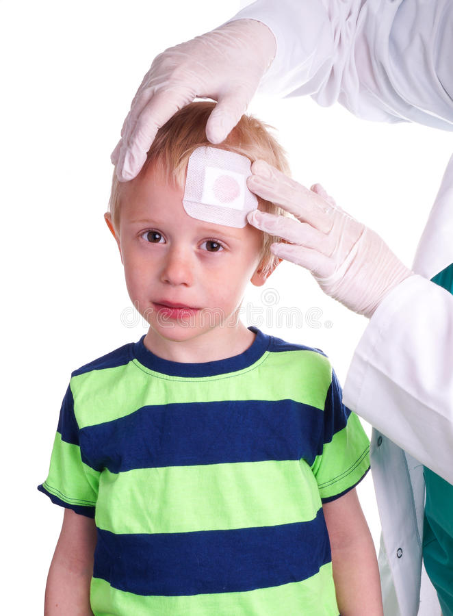 Boy has injury on forehead and gets help by the Doctor. Child gets injury on the forehead and the nurse helps with getting plaster on the wound so it can heal stock photos
