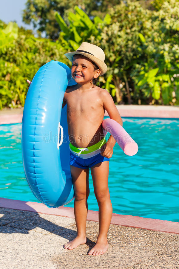 Boy in hat holding inflatable ring and pool noodle. Cute small boy in hat holding inflatable ring and pool noodle standing near the swimming pool outside in stock images