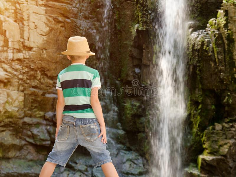 Boy in a hat looking at a waterfall. View from the back royalty free stock photo