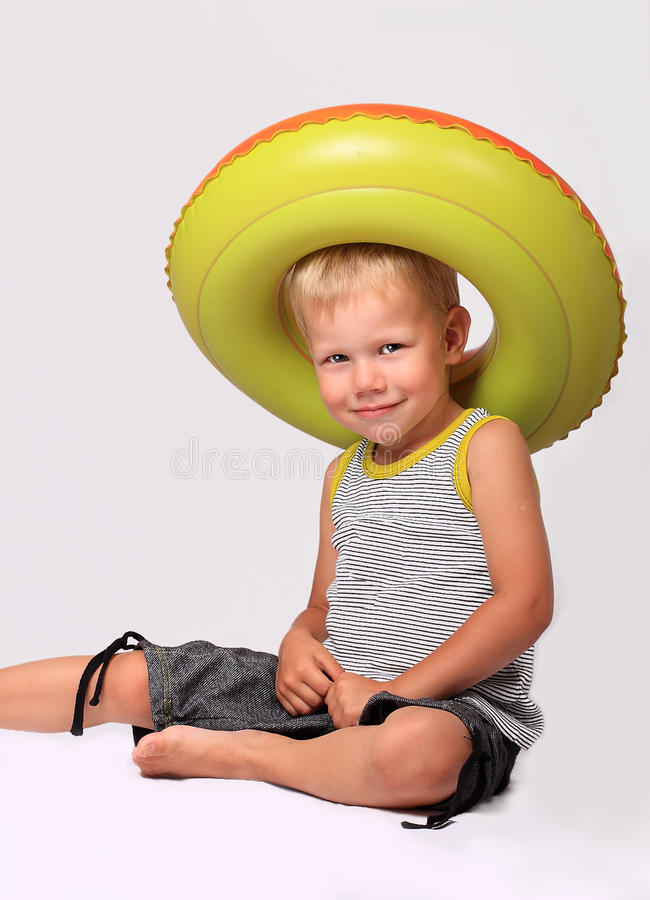 Boy in a hat from a rubber ring. Fair-haired boy plays with a rubber ring for swimming stock photography