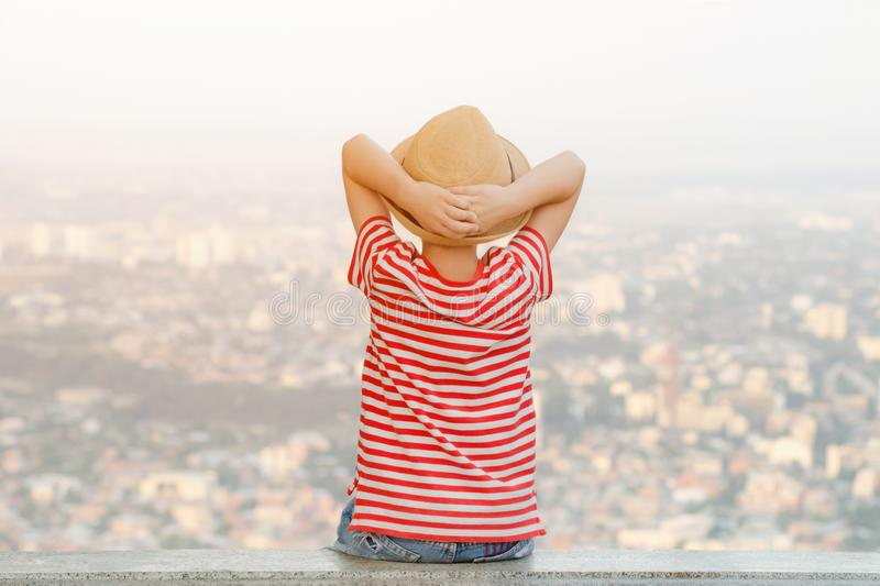 Boy in a hat sits with his hands behind his head and looks at the city from a height. Rear view stock photo