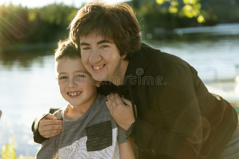 Boy have fun with his friend woman close to a lake stock photo
