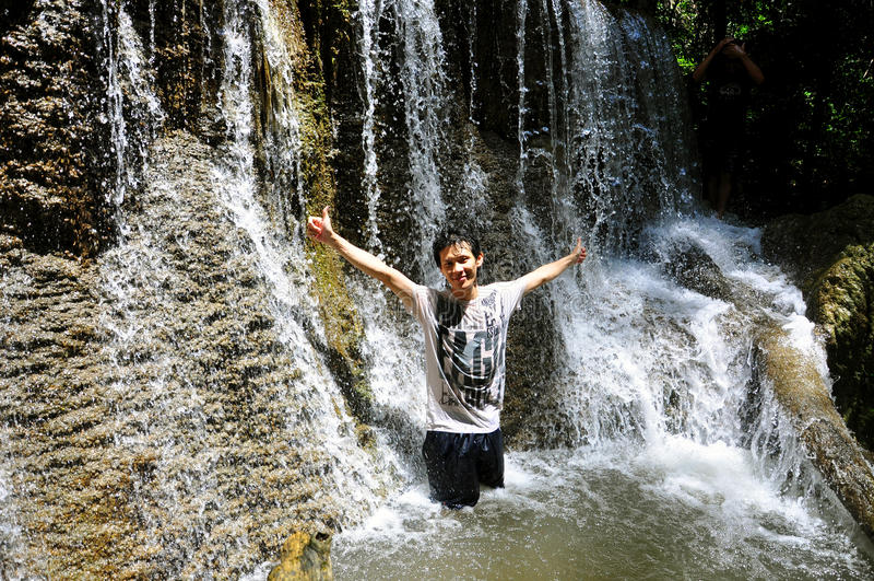 Boy having fresh under waterfall stock images