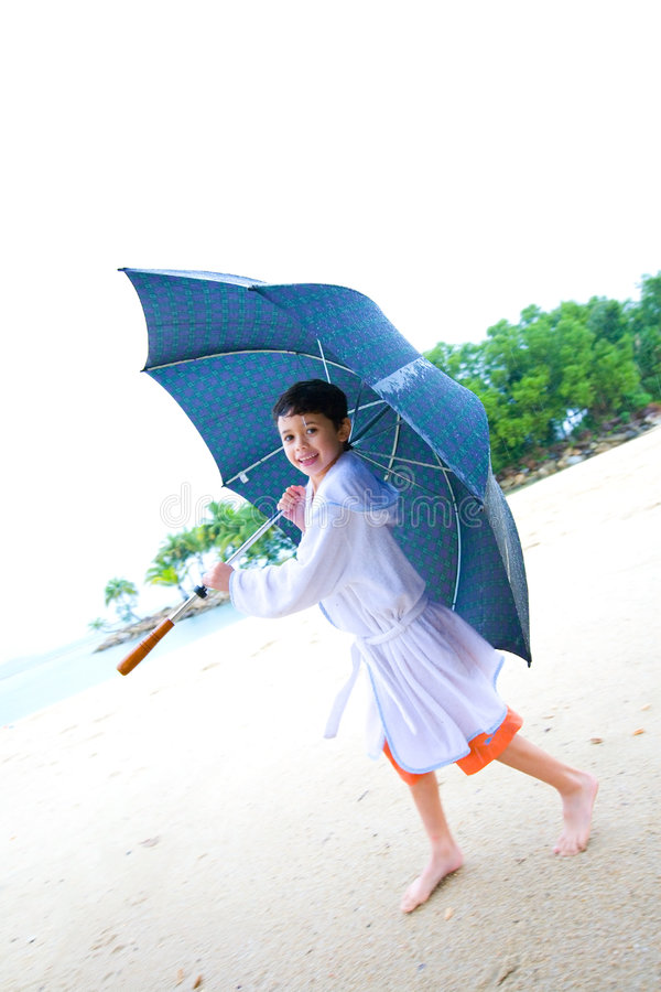 Boy having fun with big umbrella at the beach royalty free stock photo