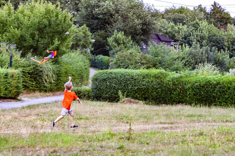 Boy having fun flying a kite in summer stock image