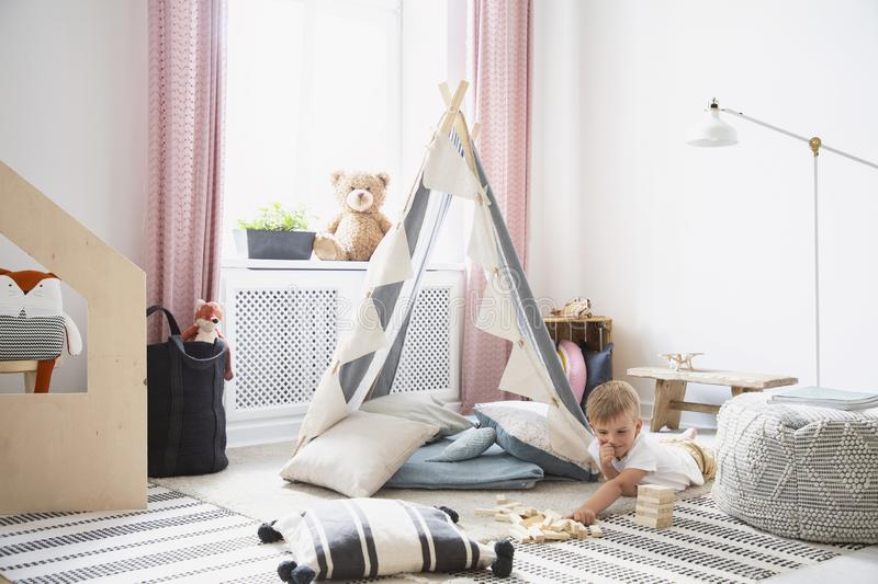 Boy having fun in a playroom interior with a tent, pillow and blocks royalty free stock image