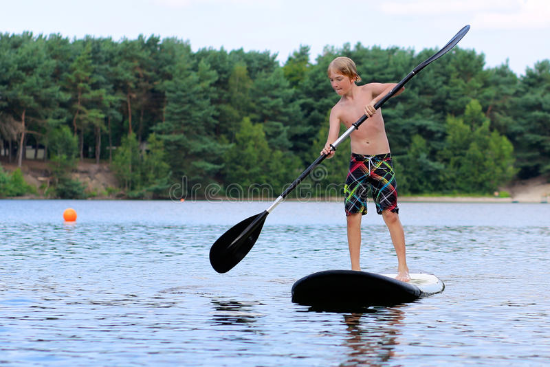 Boy having fun with stand up paddle on the lake royalty free stock photos