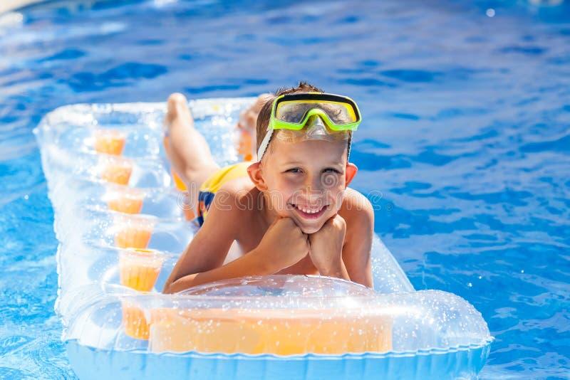 Boy having fun in swimming pool stock photo