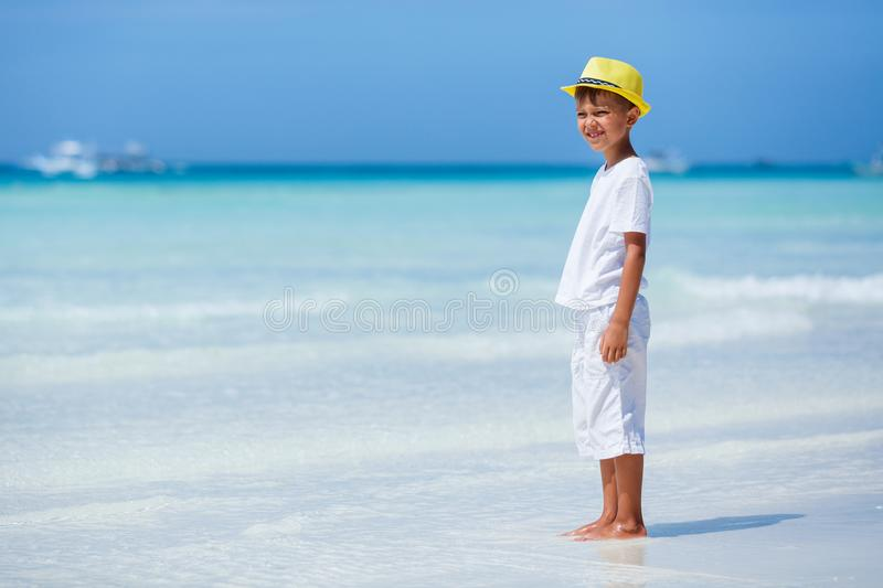Boy having fun on tropical ocean beach. Kid during family sea vacation. Little boy wearing white having fun on tropical ocean beach. Kid during family sea royalty free stock images