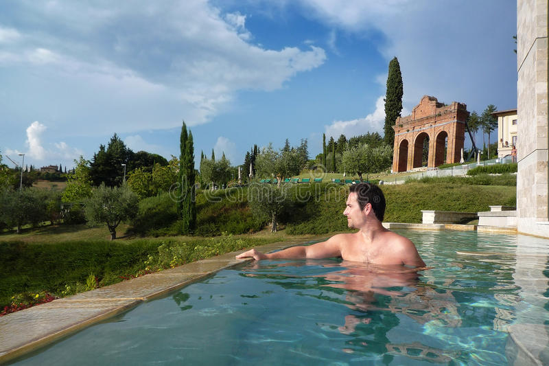 Boy having a thermal bath in the green of Tuscany. This boy is having a thermal bath in a famous and historical spa of Tuscany royalty free stock images