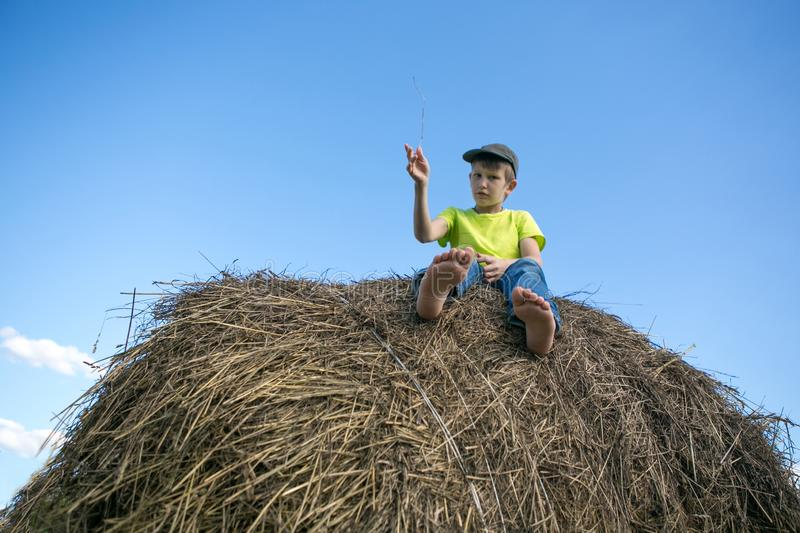 The boy on the haystack. Bare feet. Blue sky. Summer day royalty free stock photo