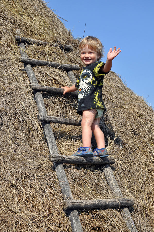 Boy on a haystack in a Russian village royalty free stock images