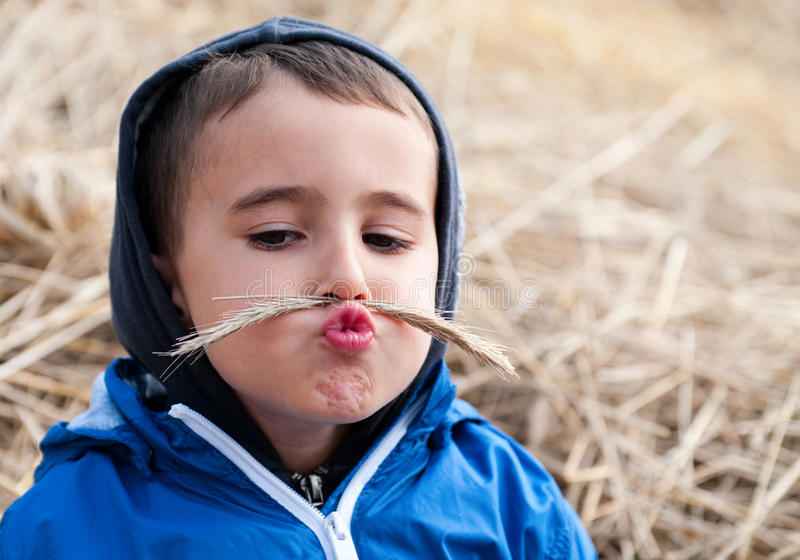 Boy in haystack with toy moustaches. Made of spikelets stock photo