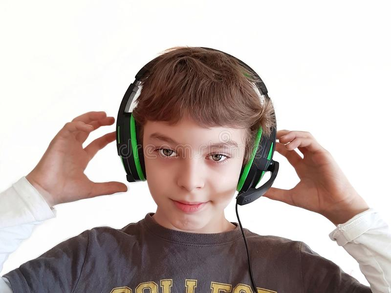 Boy with headphone listens to music on white background. Boy with headphone on white background. Teen listens music or plays computer games. Teen still-life royalty free stock photo