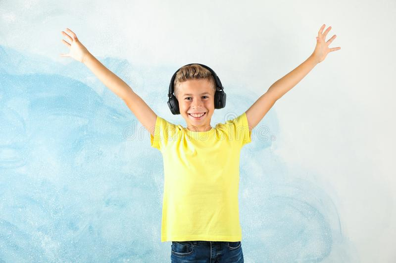 Boy with headphones against color background stock photo