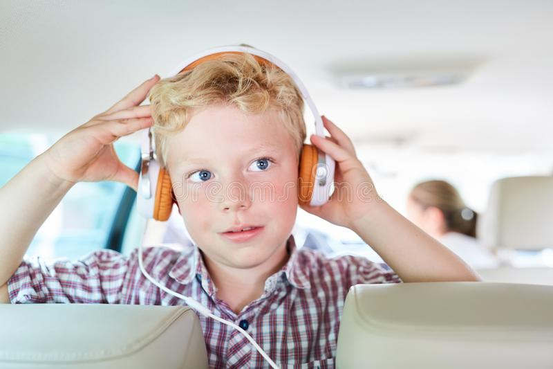 Boy with headphones in the car listens to music. Boy with headphones in the car listens to streaming music online on the journey stock image