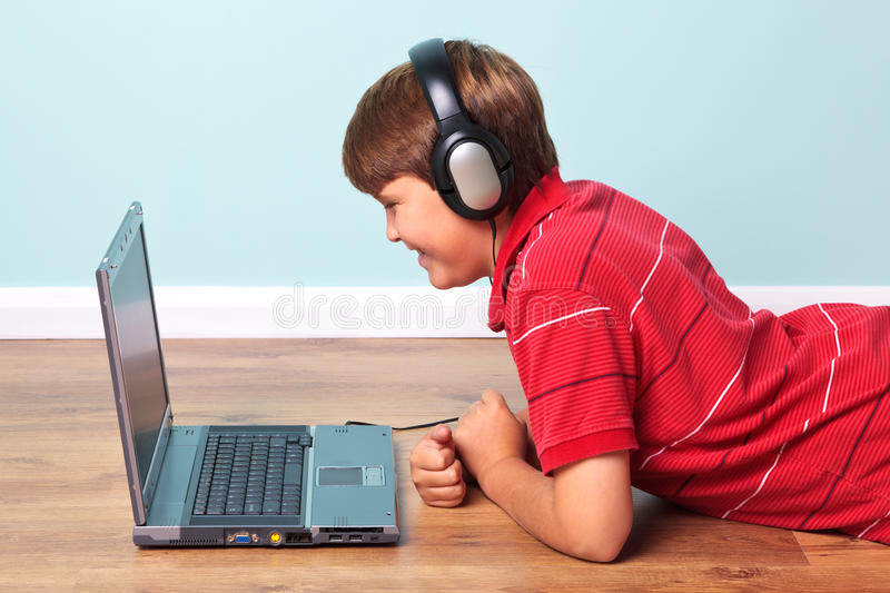 Download Boy With Headphones Looking At Laptop Stock Image - Image: 21461305