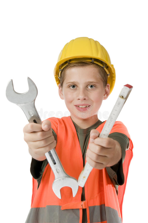 Boy with helmet holding tools. Frontal torso view of a 13 year old male teenager with yellow construction helmet and orange vest against white background into stock photography