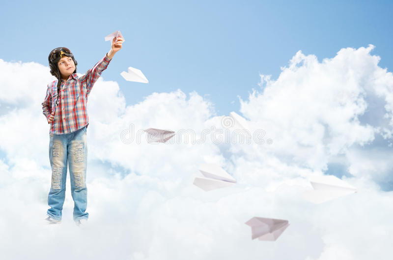 Boy dreams of becoming a pilot. Boy in helmet pilot launches paper airplanes in the clouds stock photo