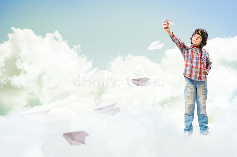 Boy dreams of becoming a pilot. Boy in helmet pilot launches paper airplanes in the clouds royalty free stock photography