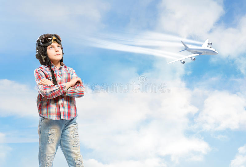 Boy in helmet pilot dreaming of becoming a pilot. Boy in helmet pilot stands with his arms crossed in the clouds, dreaming of becoming a pilot stock photos