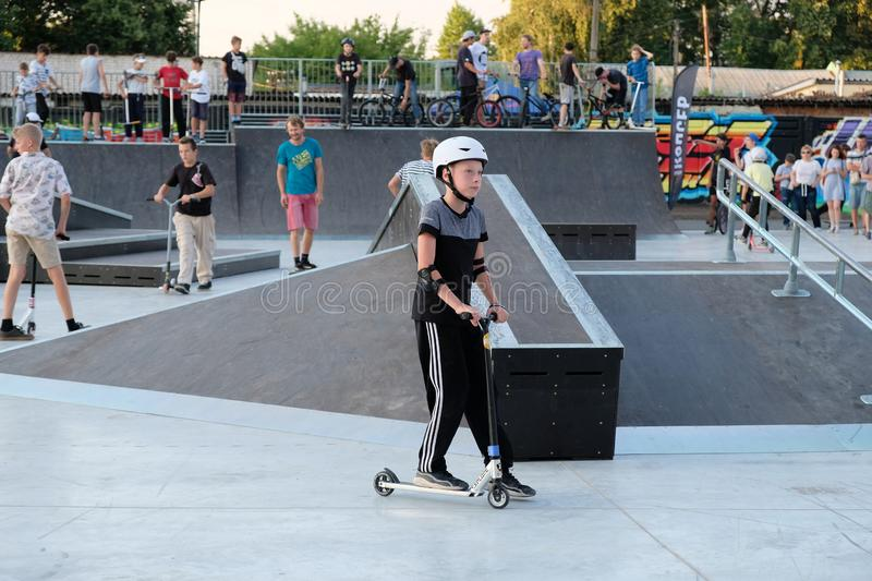 A boy in a helmet and protection on his elbows riding on a roller coaster on a scooter. stock images