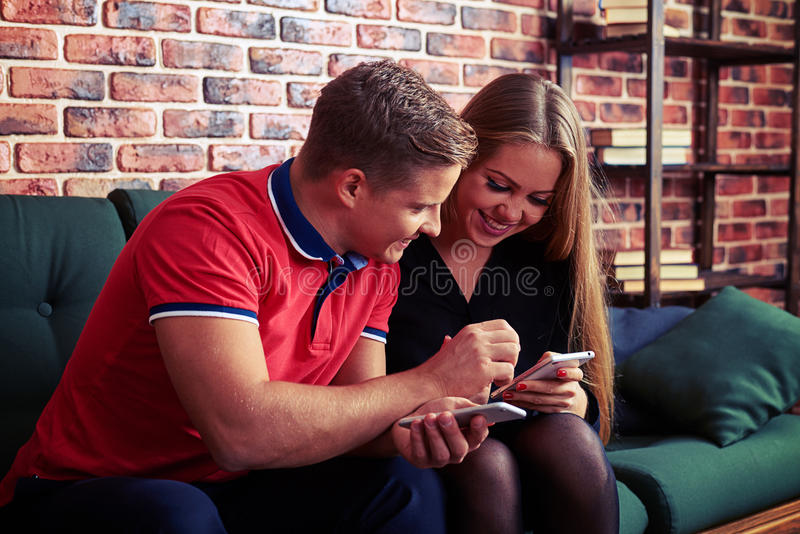 Boy helping girlfriend with smartphone when they are sitting tog stock image