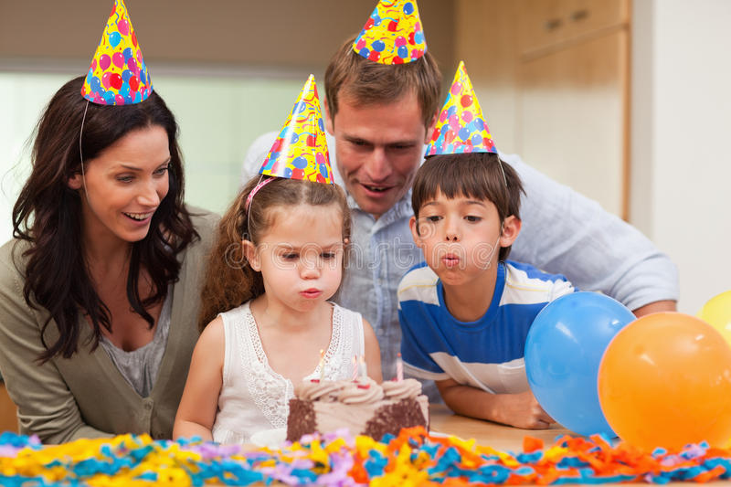 Boy helping his little sister to blow out the candles on her birthday cake. Young boy helping his little sister to blow out the candles on her birthday cake stock images