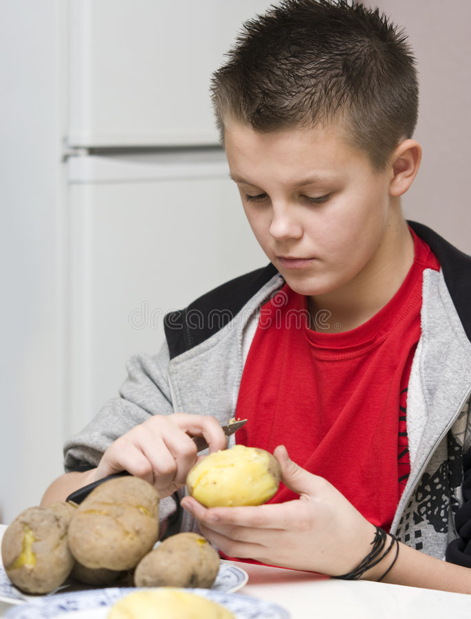 Boy helping mum in kitchen royalty free stock photo